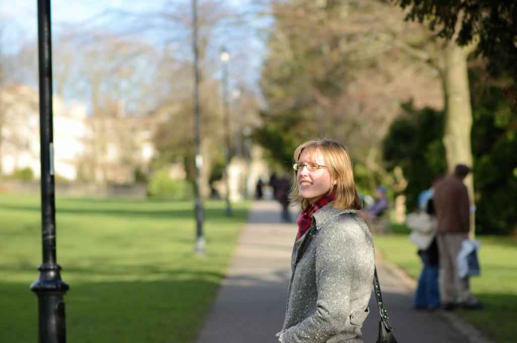 The author (Clare) enjoying a calm moment among the trees whilst walking in a park on a bright winter's day.