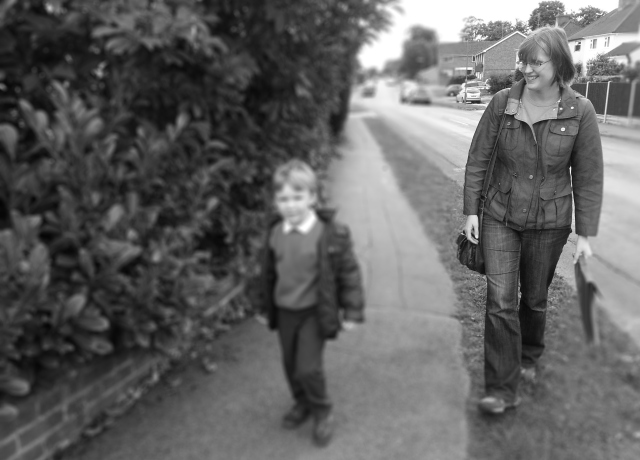 A Mum walking with her son to school. The pair look happy and content to be walking to school together. The mum is carrying her son's school book bag. She is smiling and looking proudly at her son. Her son looks relaxed and confident as he walks beside her. He is dressed smartly in his uniform, ready for school.