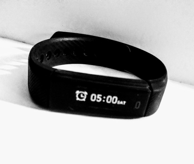 A smart wrist watch showing the alarm symbol and the time of the morning wake up alarm set to the early hour of 5am . All set ready to help the person wearing the watch wake up earlier.