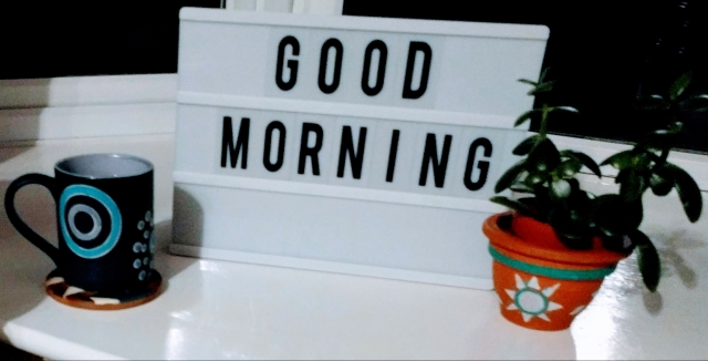 "A letters board completed with the words ""good morning"", all set up ready to  greet the early riser who has achieved their goal of waking up earlier. It is a calm, welcoming scene: A plant accompanies the letters board on the right hand side and a warm drink in a mug and placed on a coaster is waiting to be enjoyed on the left hand side of the letters board."