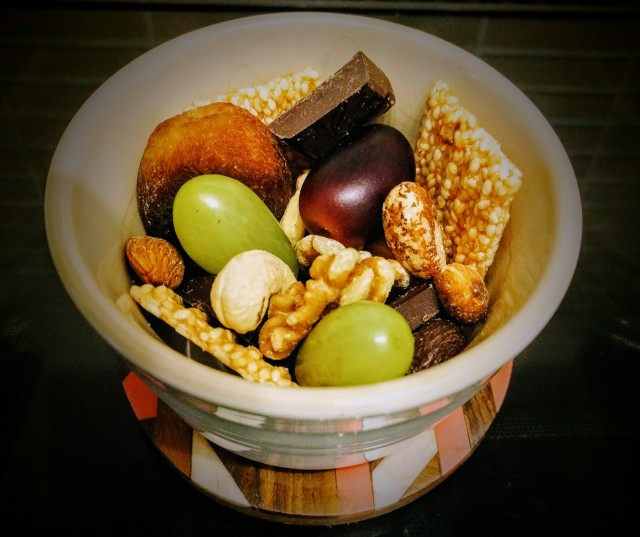 A small Ramekin, seated on a colourful coaster,  filled with a tasty looking snack. The snack contains a selection of fresh fruit, dried fruit, nuts, seeds and chocolate.
