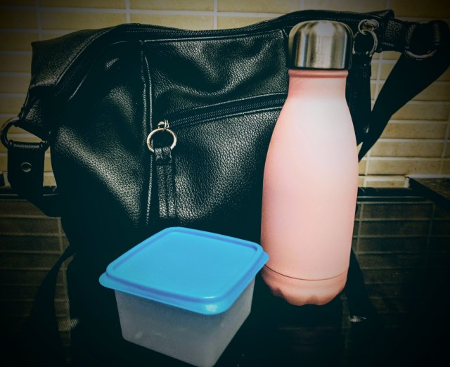 A handbag is packed and ready for leaving the house and is placed on the kitchen worktop along with a travel water bottle and a plastic snack pot. This demonstrates that the morning snack and drink can be easily transported in a handbag for days out, work or when travelling.