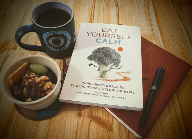 "The book ""Eat Yourself Calm"" which was used to research the morning snack is placed on a table with a notebook and pen. These items are accompanied by a mug of black coffee and a Ramekin containing the morning snack pot. The front cover of the book ""Eat Yourself Calm"" is shown clearly for ease of recognition, should the reader wish to search out the book for themselves."