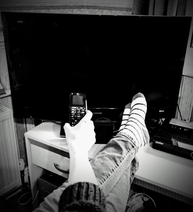 There is a large telvision screen. In front of the television screen are a persons outstretched legs resting on the television stand. The person has cozy casual socks on their feet and their feet  are crossed. The person has their arm outstetched towards the T.V. screen and is holding a T.V. remote control pointing at the screen. It looks as though the person is lounging in front of the television and is either about to change the channel or switch the T.V. on/off.