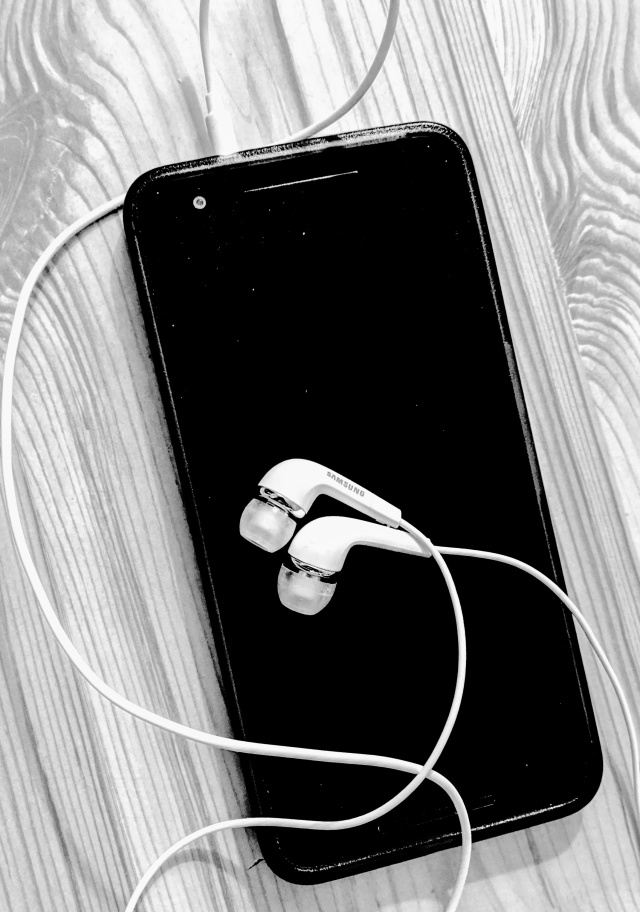 A smart phone resting on a table with some ear-buds plugged in ready for use. This shows how you can set your phone up to listen to Podcasts while you are on the go around the house or if you wish to step out into the garden.
